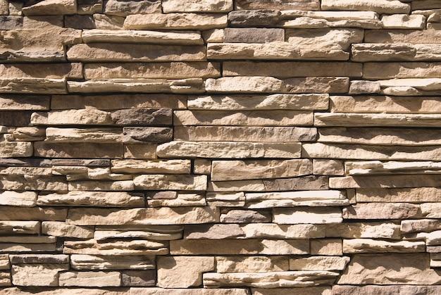 Fundo de parede de pedra artificial com luz solar intensa e sombras Foto Premium