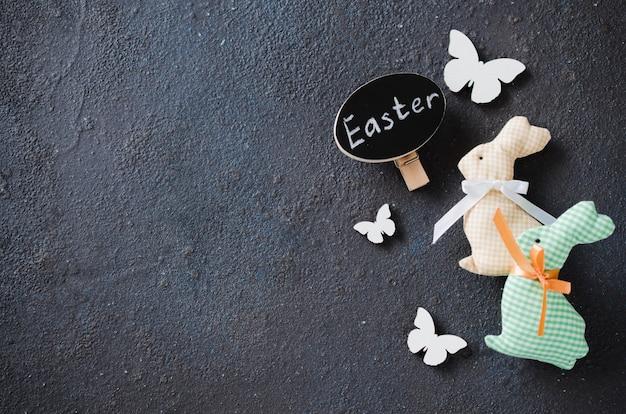 Fundo de páscoa com coelho decorativo, borboletas e inscrição páscoa. Foto Premium