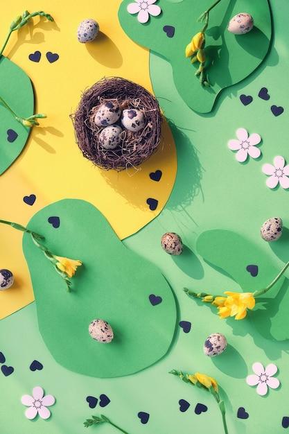 Fundo de páscoa de design gráfico colorido. postura plana, vista superior com ovos de codorna, tesoura, coração com texto páscoa, flores de freesia. Foto Premium
