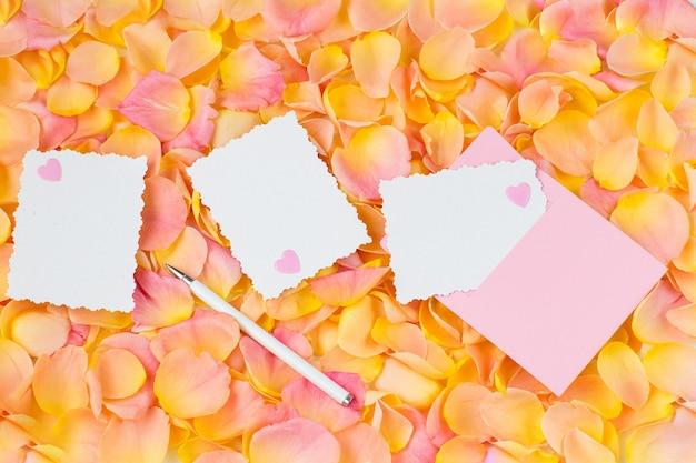 Fundo de pétalas de rosa cor de rosa, envelope rosa, corações, caneta e folhas de papel Foto Premium