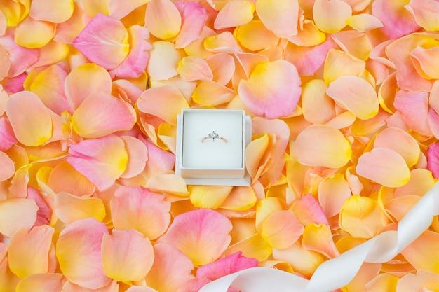 Fundo de pétalas de rosa, fita e anel de noivado com diamante Foto Premium