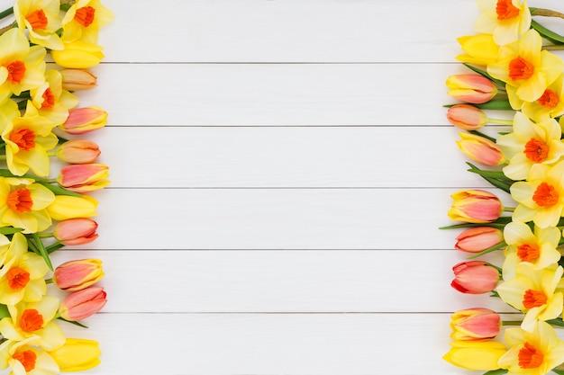Fundo de primavera. tulipas e narciso em fundo branco de madeira. espaço da cópia Foto Premium
