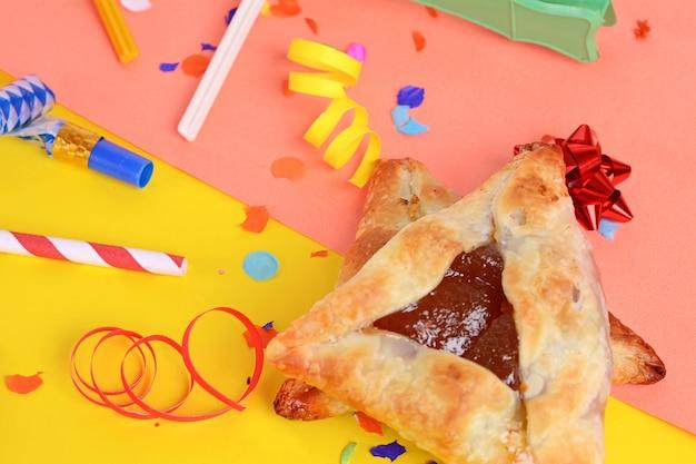 Fundo de purim com fantasia de festa e biscoitos hamantaschen. Foto Premium