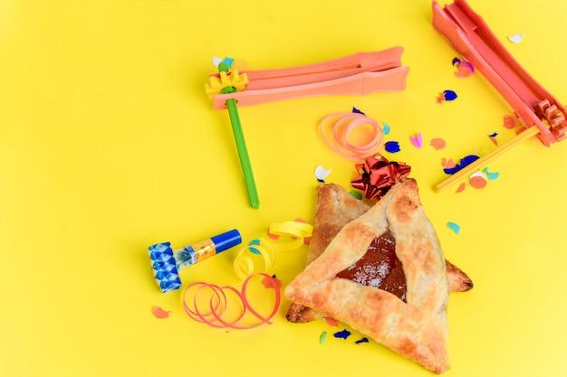 Fundo de purim com fantasia de festa e biscoitos hamantaschen Foto Premium