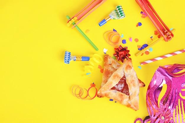 Fundo de purim com máscara de carnaval, fantasia de festa e biscoitos hamantaschen. Foto Premium