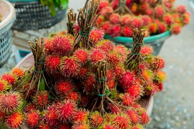 Fundo de rambutans de frutas frescas, rambutans vermelhos e rambutans amarelos em um mercado local, Foto Premium