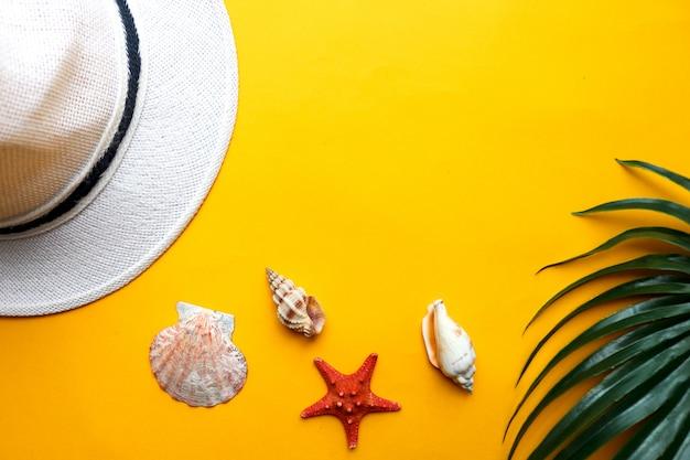 Fundo de verão com conchas, chapéu de praia e folha de palmeira sobre fundo amarelo. verão, férias na praia e conceito de viagem Foto Premium