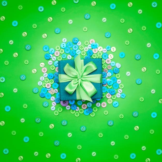 Fundo decorativo com botões coloridos em massa e caixa de presente. Foto Premium