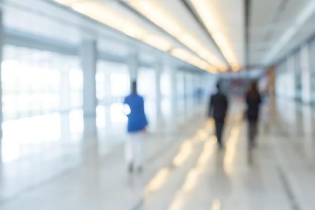 Fundo desfocado de empresários andando no corredor de um centro de negócios Foto Premium