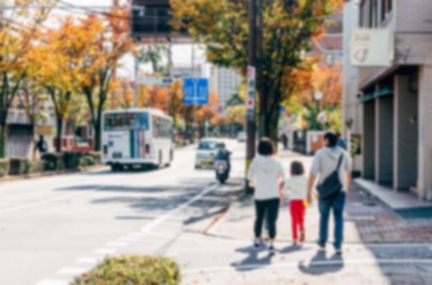 Fundo desfocado. família japonesa turva a pé em uma rua da cidade. Foto Premium