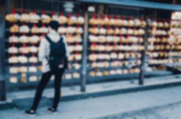 Fundo desfocado. mulher turva esperando no templo xintoísmo. Foto Premium
