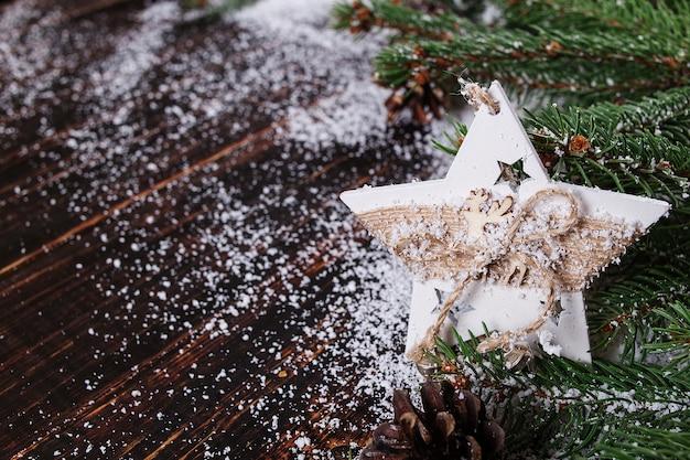 Fundo do conceito de natal, decoração artesanal de estrelas e árvores de natal verdes em uma mesa de madeira, tracejada pela neve branca Foto Premium