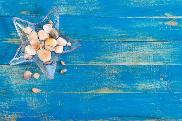 Fundo do mar tropical. conchas diferentes, em uma tigela de vidro em forma de estrela do mar nas placas azuis, vista superior. espaço livre para inscrições. tema de verão. Foto Premium
