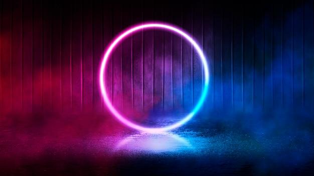 Fundo do palco vazio, quarto. reflexão no pavimento molhado, concreto. luzes desfocadas de néon. figura de círculo de néon no centro, fumaça Foto Premium