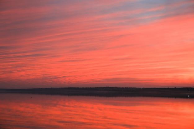 Fundo dramático do céu do por do sol com rio, nuvens impetuosas, cor amarela, alaranjada e cor-de-rosa, fundo da natureza. lindos céus Foto Premium
