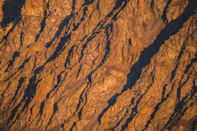 Fundo ensolarado da natureza das montanhas rochosas na luz solar. textura de montanha natural vívida de grandes rochas ásperas. quadro completo de superfície escarpada gigante brilhante. close-up da montanha rochosa. avião de pedras brilhantes no pôr do sol. Foto Premium