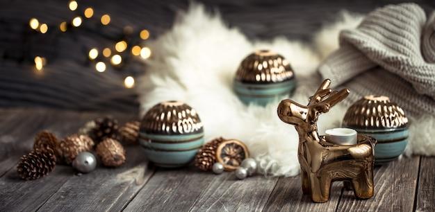 Fundo festivo de natal com cervo de brinquedo com uma caixa de presente, fundo desfocado com luzes douradas, fundo festivo em mesa de deck de madeira Foto gratuita