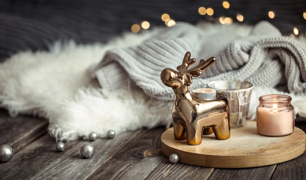 Fundo festivo de natal com cervo de brinquedo, fundo desfocado com luzes douradas e velas, fundo festivo na mesa de deck de madeira e suéter de inverno no fundo Foto gratuita