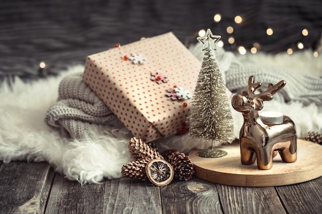 Fundo festivo de natal com veado de brinquedo com uma caixa de presente, fundo desfocado com luzes douradas, fundo festivo na mesa de deck de madeira e suéter aconchegante no fundo Foto gratuita