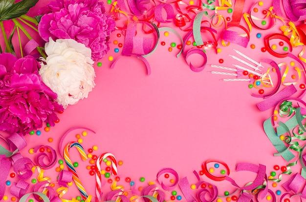 Fundo festivo. peônias rosa e brancas em um fundo rosa com um quadro de doces e enfeites de natal. Foto Premium