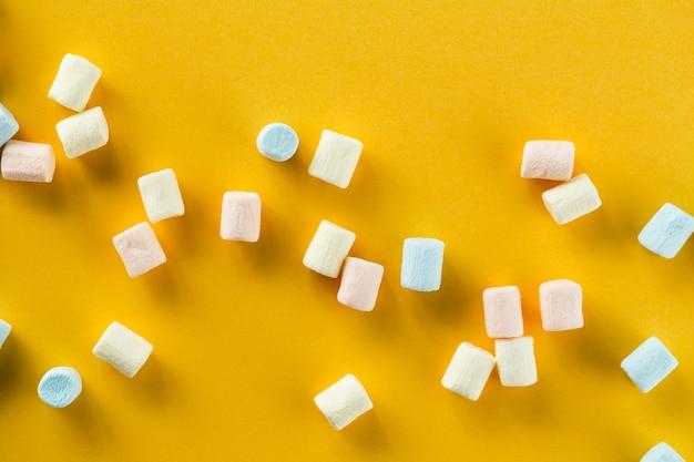 Fundo laranja com marshmallows coloridos Foto gratuita