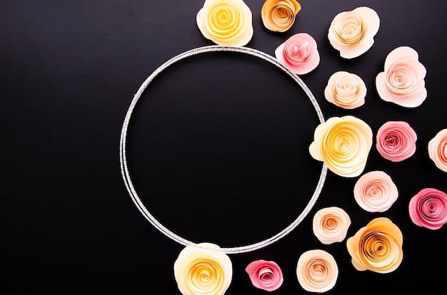 Fundo liso leigos preto com moldura de flores de papel bonito Foto gratuita