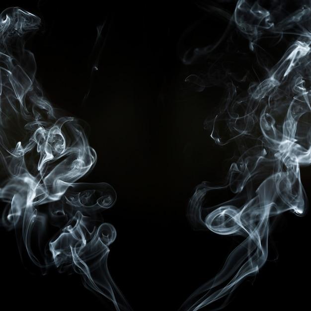 Fundo preto com duas silhuetas de fumaça em movimento Foto gratuita