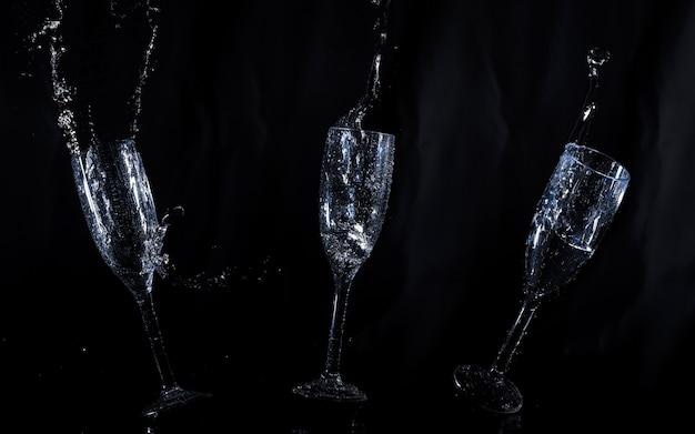 Fundo preto com vidros de água flutuando Foto gratuita