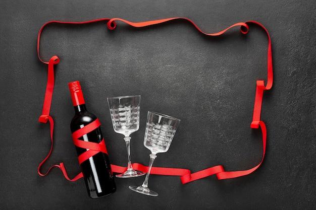 Fundo preto concreto com uma fita vermelha, uma garrafa de vinho tinto e uma caixa de presente. conceito de férias, parabéns, data. Foto Premium