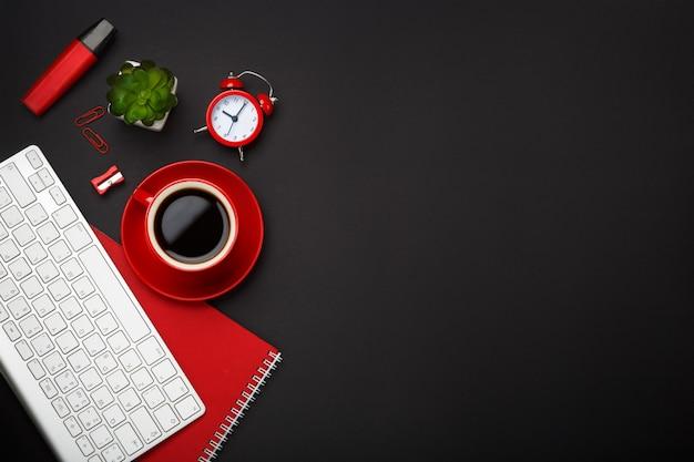 Fundo preto copo de café vermelho nota almofada despertador teclado flor espaço em branco Foto Premium