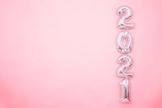 Fundo rosa claro com balões prateados de ano novo em forma de números no lado direito, conceito de ano novo Foto gratuita