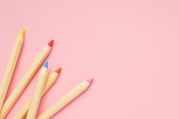 Fundo rosa com lápis comuns coloridos de madeira. de volta à escola. Foto Premium