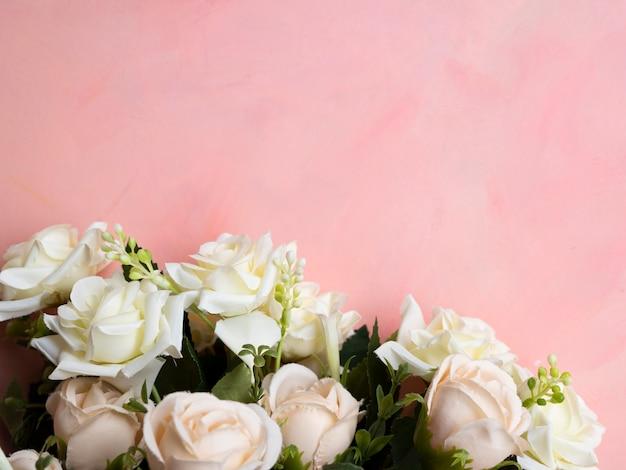 Fundo rosa com moldura de rosas brancas Foto gratuita
