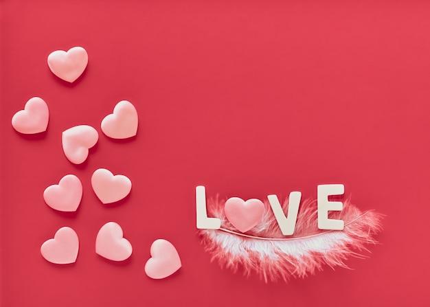 Fundo rosa de dia dos namorados com corações rosa e a palavra amor forrada com letras de madeira brancas na pena branca. dia das mães, cartão comemorativo de 8 de março Foto Premium