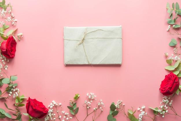 Fundo rosa romântico com moldura feita de flores rosas vermelhas e presente Foto Premium