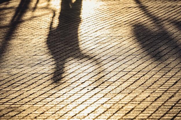 Fundo urbano abstrato com sombra difusa do homem que anda no por do sol, conceito da solidão. Foto Premium