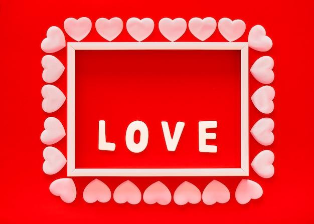 Fundo vermelho do dia dos namorados com moldura branca, a palavra amor e corações rosa. dia das mães, cartão comemorativo de 8 de março Foto Premium