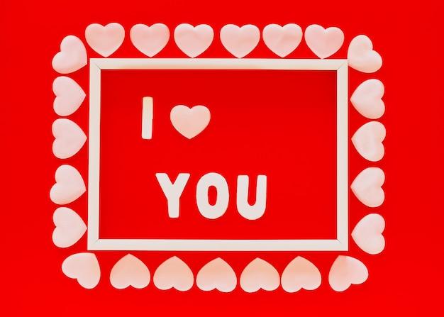 Fundo vermelho do dia dos namorados com moldura branca, a palavra i you e corações rosa. dia das mães, cartão de 8 de março, 14 de fevereiro. Foto Premium