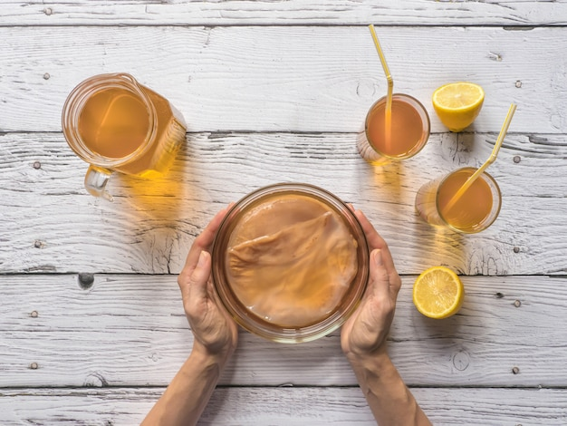Fungo de kombucha. bebida de chá fermentado orgânico em uma mesa de madeira branca. Foto Premium