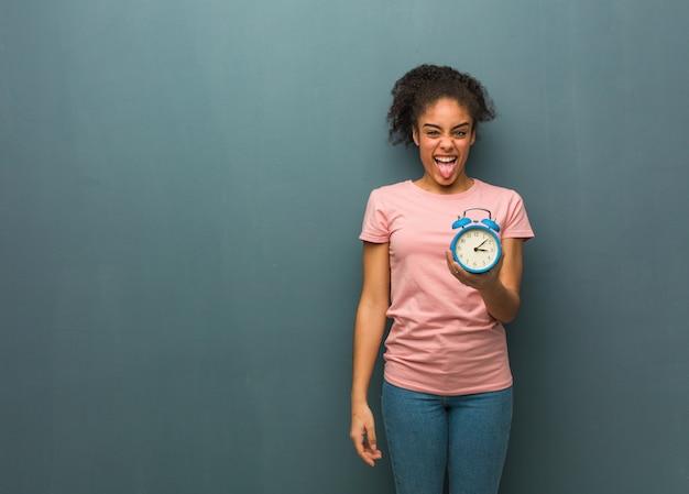 Funnny novo da mulher negra e língua mostrando amigável. ela está segurando um despertador. Foto Premium