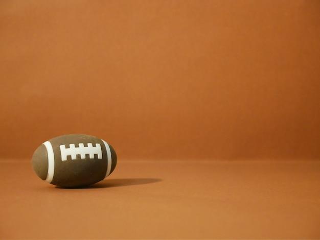 Futebol americano com espaço da cópia no fundo marrom. Foto Premium