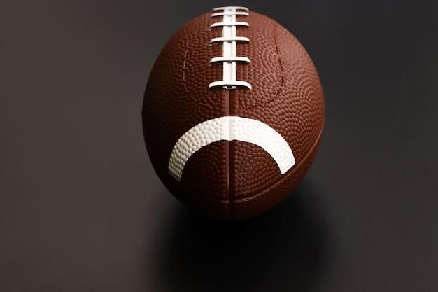 Futebol americano isolado no fundo preto. conceito de objeto de esporte Foto Premium