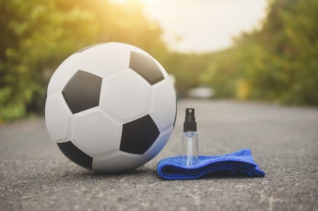 Futebol futebol e spray de álcool para limpar o vírus corona covid 19, novo normal Foto Premium