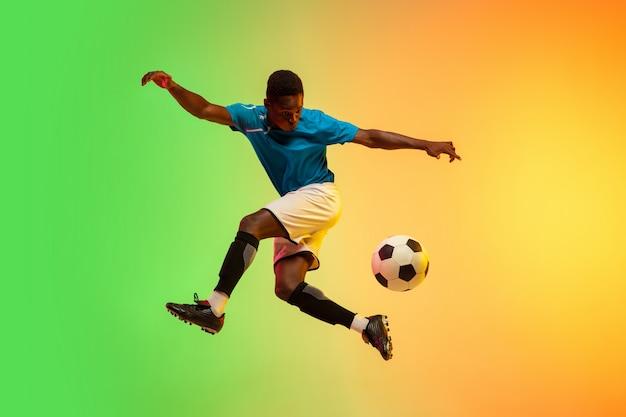 Futebol masculino, jogador de futebol treinando em ação isolado em estúdio gradiente em luz de néon Foto gratuita