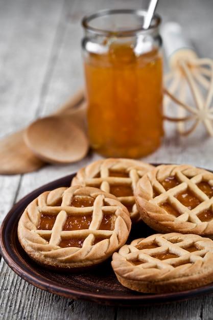 Galdérias cozidas frescas com doce do doce de fruta do marmelada ou do abricó e no utensílio cerâmico da placa e da padaria da cozinha. Foto Premium