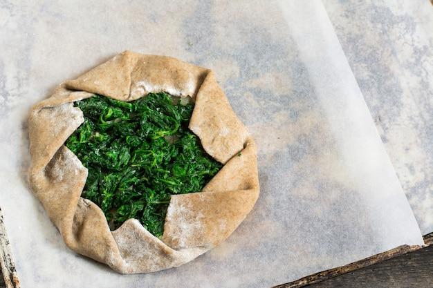 Galette de verão com espinafre. comida de verão, torta aberta, processo de cozimento, massa crua. Foto Premium