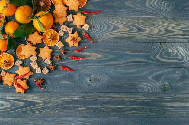 Galho de árvore de natal, biscoitos de natal e laranja seca no antigo fundo de madeira azul. pão caseiro cozido fresco. Foto Premium