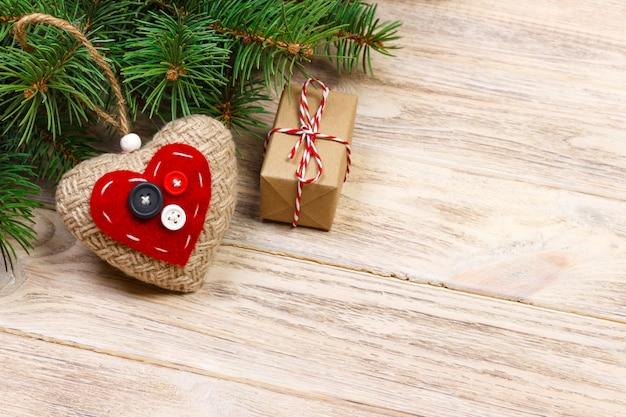 Galho de árvore de natal com caixa de presente vermelha e corações vermelhos na mesa de madeira. vista superior com espaço de cópia Foto Premium