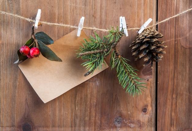 Galho de árvore de natal, pinha e bagas de inverno em uma corda com prendedores de roupa. desejando um feliz natal Foto Premium