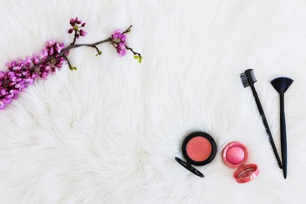 Galho de flor roxa com pó compacto e pincéis de maquiagem no cenário de peles Foto gratuita